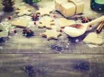 Galletas jengibre, cuchara con la harina en un fondo de madera Imagen de archivo libre de regalías