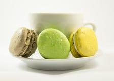 Galletas multicoloras de los macarrones y taza del café con leche Imagenes de archivo