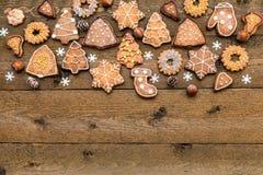 Galletas, nueces y copos de nieve del pan de jengibre de la Navidad en fondo de madera con el espacio para su texto foto de archivo libre de regalías