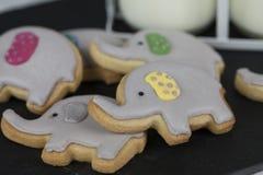 Galletas o galletas del partido del elefante con dos pequeños jarros de leche Fotos de archivo