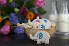 Galletas o galletas del partido del elefante con dos pequeños jarros de leche Imagenes de archivo
