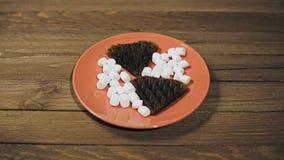 Galletas oscuras cocidas en la forma del corazón en la placa, postre romántico
