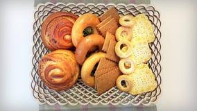 Galletas, panecillos, rollos en una cesta en la tabla Foto de archivo