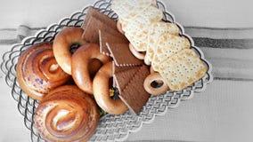 Galletas, panecillos, rollos en una cesta en la tabla Foto de archivo libre de regalías