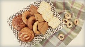 Galletas, panecillos, rollos en una cesta en la tabla Imagen de archivo libre de regalías