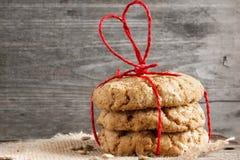 Galletas para el día del ` s de la tarjeta del día de San Valentín con la cinta en forma de corazón roja en la madera Imagen de archivo libre de regalías