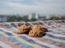 Galletas pasa y nueces de macadamia en fondo de la naturaleza y textura de la tela de la raya foto de archivo libre de regalías
