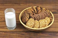 Galletas, pilas de galletas y un vidrio de leche Imágenes de archivo libres de regalías