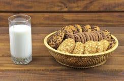 Galletas, pilas de galletas y un vidrio de leche Fotografía de archivo libre de regalías