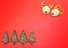 Galletas principales del chocolate de los ciervos y galletas de la baya del árbol de navidad en fondo plástico rojo Foto de archivo