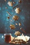 Galletas que caen con té caliente Levitación del pan de jengibre con la salsa y el canela de chocolate en fondo oscuro Humor de l imagen de archivo libre de regalías