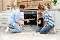 Galletas que cuecen de la familia feliz en horno imagen de archivo libre de regalías