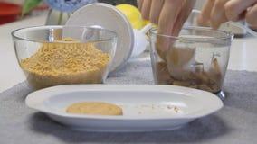 Galletas que se agrietan y de mezclas mientras que cocina y hace la torta de la crema del queso con los arándanos metrajes
