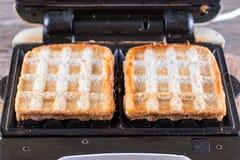 Galletas, queso y jamón en el hierro de galleta imagenes de archivo