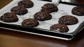 Galletas recientemente cocidas del chocolate en el molde para el horno en un primer de la tabla almacen de metraje de vídeo