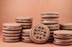 Galletas redondas del bocadillo del chocolate con el relleno poner crema de la vainilla en la tabla de madera marrón con el copys Imagenes de archivo