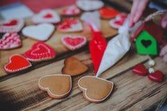 Galletas rojas del corazón en día de madera del ` s de la tarjeta del día de San Valentín del fondo Imágenes de archivo libres de regalías