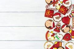 Galletas rojas del pan de jengibre de la Navidad en fondo de madera Fotografía de archivo libre de regalías