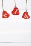 Galletas rojas en una forma del corazón en una tabla de madera fotos de archivo