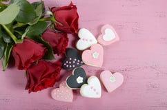 Galletas románticas del rosa de la forma del corazón, blancas y negras con las rosas rojas Imagen de archivo