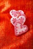 Galletas rosadas blancas festivas del corazón en el contexto rojo del brillo Imagen de archivo libre de regalías