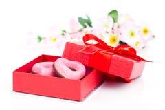 Galletas rosadas del corazón para el día de tarjetas del día de San Valentín en regalo rojo Fotografía de archivo libre de regalías