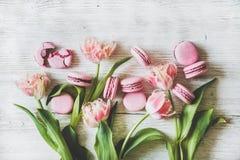 Galletas rosadas dulces del macaron y flores frescas del tulipán de la primavera fotografía de archivo libre de regalías