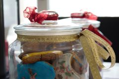 Galletas sabrosas coloridas hechas en casa deliciosas de la Navidad y en tarros adornados hermosos con una vela en la parte poste imagen de archivo
