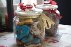 Galletas sabrosas hechas en casa deliciosas de la Navidad y en tarros adornados hermosos con una vela en la parte posterior fotos de archivo libres de regalías
