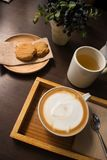 Galletas, té, y café en una tabla de madera oscura Foto de archivo libre de regalías