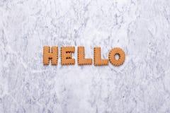 Galletas tasy de las letras hola en el fondo de mármol imagenes de archivo