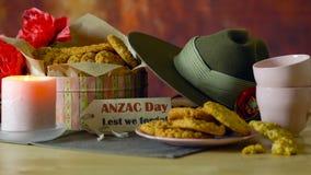 Galletas tradicionales de ANZAC en el vintage que fija con el sombrero de vago australiano del ejército metrajes