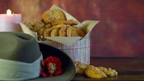 Galletas tradicionales de ANZAC en el vintage que fija con el sombrero de vago australiano del ejército almacen de metraje de vídeo