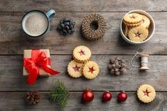 Galletas tradicionales de Linzer con el atasco dulce y decoraciones de la Navidad en fondo de madera Imágenes de archivo libres de regalías