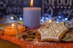 Galletas, velas, almendras y especias del jengibre de la Navidad en un papel rojo Imagen de archivo