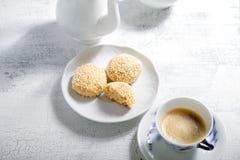 Galletas y café de almendra en la tabla blanca Imagen de archivo