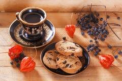 Galletas y café de harina de avena en luz del sol en un fondo de madera con el physalis y las bayas salvajes del bosque Fotos de archivo