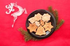 Galletas y decoraciones de la Navidad en fondo rojo Fotos de archivo libres de regalías