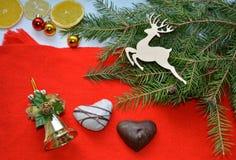 Galletas y decoraciones de la Navidad en un fondo rojo Fotografía de archivo