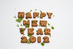 Galletas y hojas del Año Nuevo 2012 Imagen de archivo libre de regalías