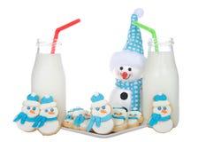 Galletas y leche de los muñecos de nieve con el muñeco de nieve aislado en blanco Imagen de archivo