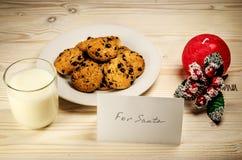 Galletas y leche para Santa Claus en una tabla de madera Imagenes de archivo