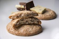 Galletas y pedazos redondos grandes de leche y de chocolate blanco Imagen de archivo