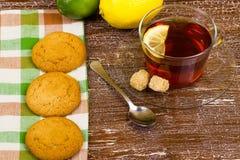Galletas y té con un limón Foto de archivo libre de regalías