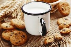 Galletas y taza con leche Fotos de archivo