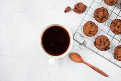 Galletas y tazas de café recientemente cocidas en la tabla de madera blanca imágenes de archivo libres de regalías