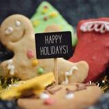 Galletas y texto de la Navidad buenas fiestas Foto de archivo libre de regalías