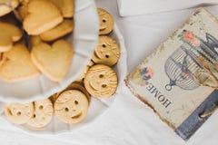 Galletas y un cuaderno en la tabla de cocina Fotografía de archivo libre de regalías