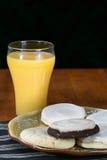 Galletas y zumo de naranja Imagenes de archivo