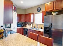 Galley Kitchen with Cherry Cabinets stock photography